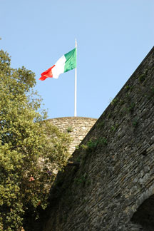 Italian flag flying on a historic tower in Bergamo